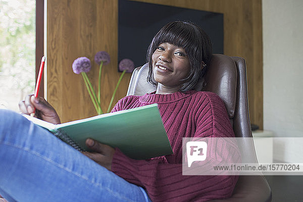 Portrait happy young woman journaling
