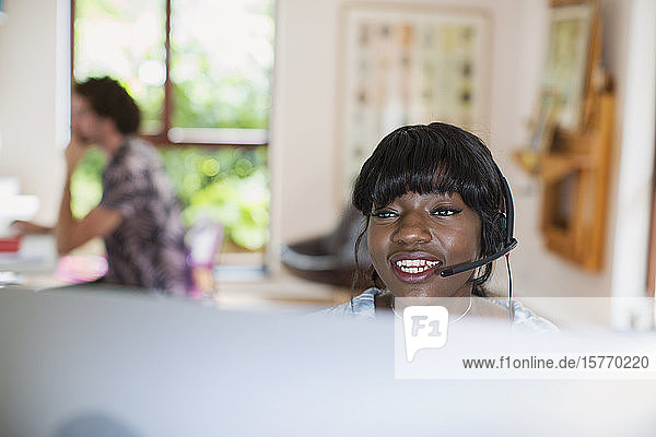 Young woman with headset working from home at computer