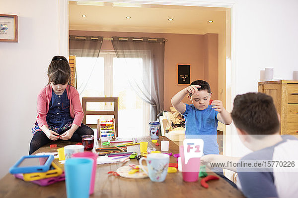 Brothers and sister playing with toys at dining table