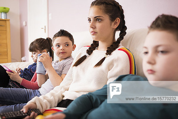 Brothers and sisters watching TV on living room sofa