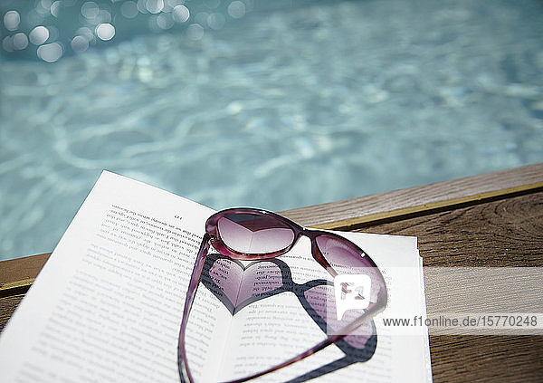 Heart-shape sunglasses on book at sunny poolside