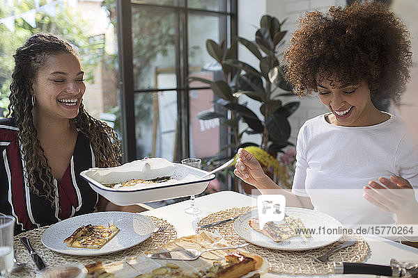 Happy young women eating lunch at dining table