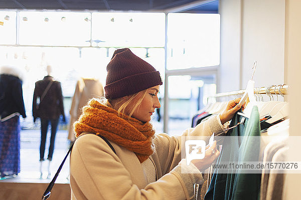 Young woman shopping in clothing store  checking price tag