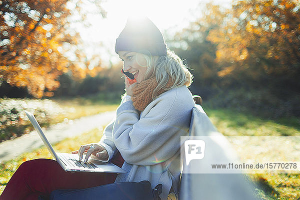Young woman using laptop and talking on smart phone on sunny autumn park bench