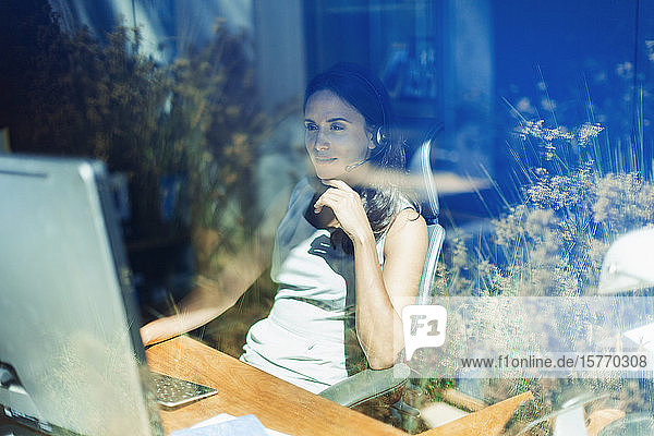 Businesswoman with headset working at computer in sunny home office