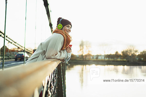 Carefree woman listening to music with headphones on autumn bridge