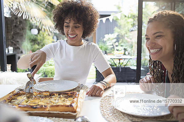 Happy young women friends slicing homemade pizza at table