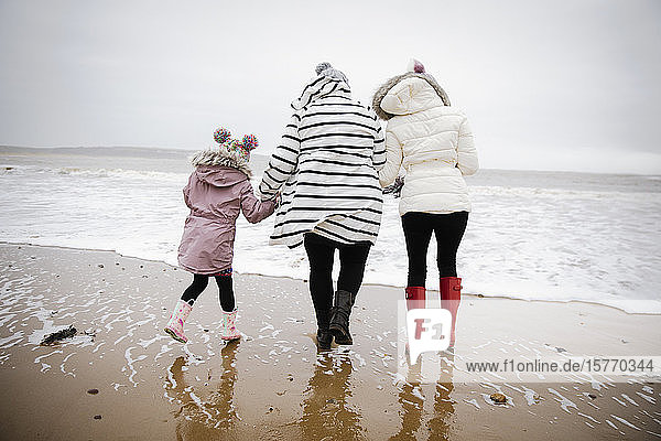 Mother and daughters in warm clothing walking on winter ocean beach