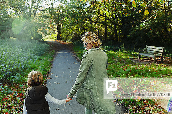Happy mother and son holding hands and walking in sunny autumn park