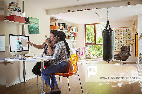 Young creative entrepreneurs working at computer in home office