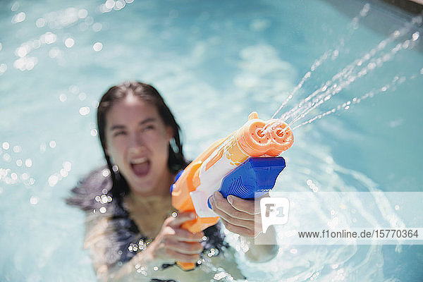 Playful woman using squirt gun in sunny summer swimming pool