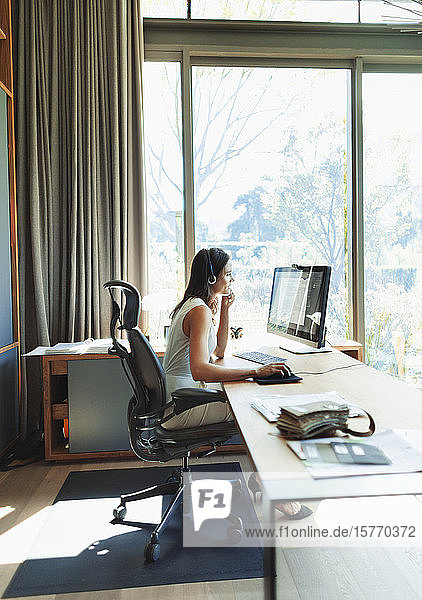 Businesswoman in headset working at computer in home office