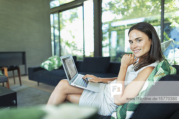Portrait confident businesswoman working from home  using laptop in living room