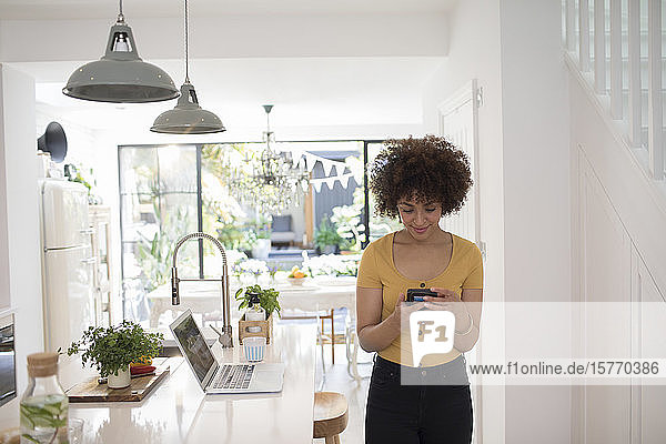 Young female freelancer using smart phone in kitchen