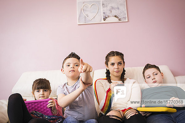 Down Syndrome boy watching TV with siblings on sofa