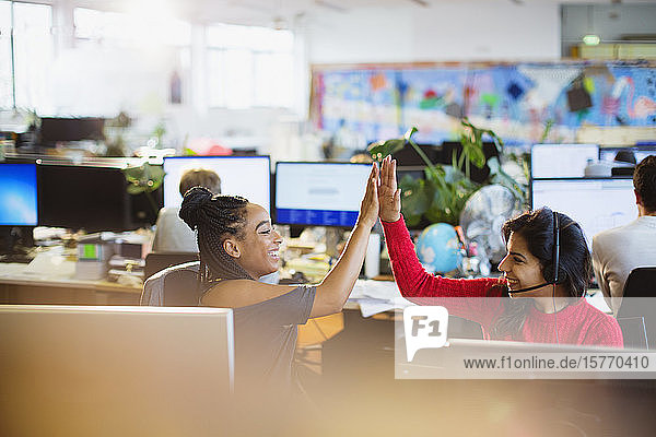 Happy businesswomen high-fiving at computers in open plan office