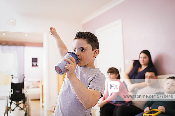 Boy with Down Syndrome drinking and cheering in living room
