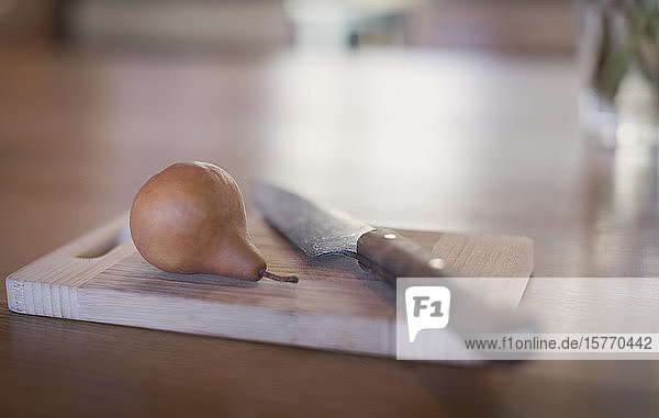 Still life knife and pear on wooden cutting board
