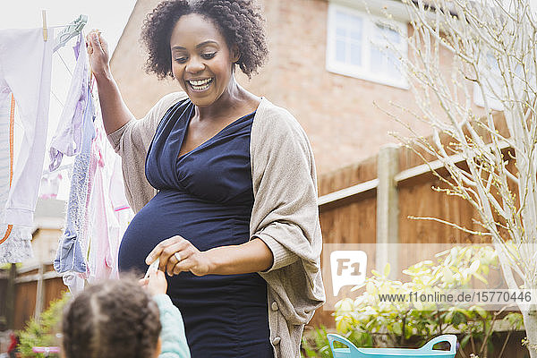 Happy pregnant woman hanging clothes on clothesline