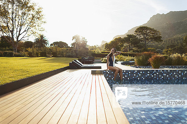 Young woman in bathing suit relaxing at sunny  luxury swimming pool  Cape Town  South Africa
