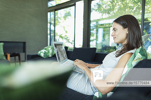 Businesswoman working from home  using laptop on living room sofa