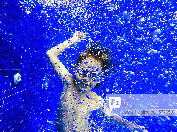Portrait playful boy swimming underwater in blue swimming pool