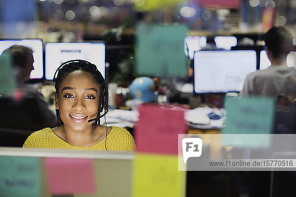 Portrait confident  smiling businesswoman with headset working at computer behind adhesive notes in office