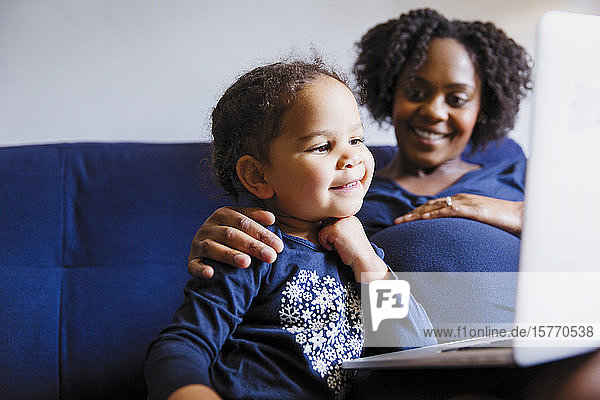 Happy pregnant mother and preschool daughter using laptop on sofa
