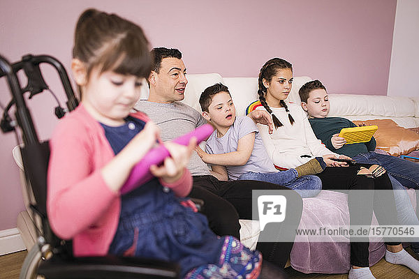 Down Syndrome family watching TV on living room sofa