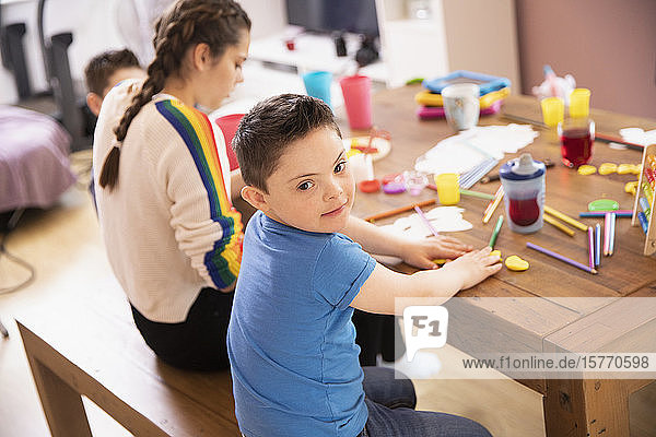 Portrait cute boy with Down Syndrome coloring at table with sister