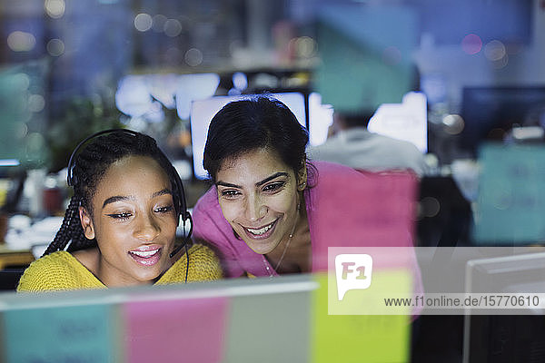 Smiling businesswomen working at computer behind adhesive notes