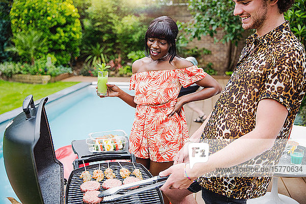 Young multiethnic couple barbecuing at poolside