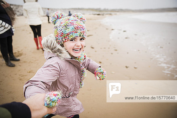 Portrait happy carefree girl in warm clothing running on winter beach