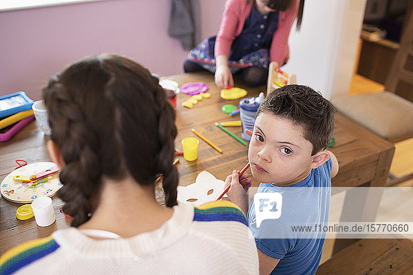 Portrait cute boy with Down Syndrome coloring at table with siblings
