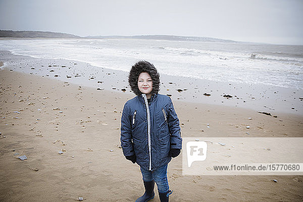 Portrait confident boy in fur hooded jacket on winter ocean beach
