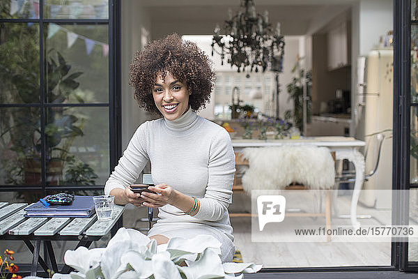 Portrait happy young woman using smart phone on patio