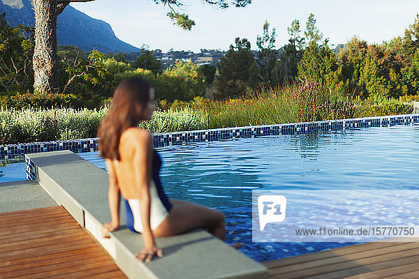 Woman in bathing suit relaxing at idyllic  tranquil swimming pool