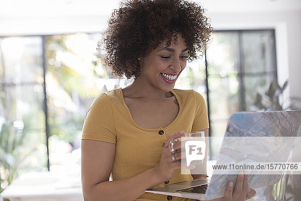 Happy young female freelancer working at laptop