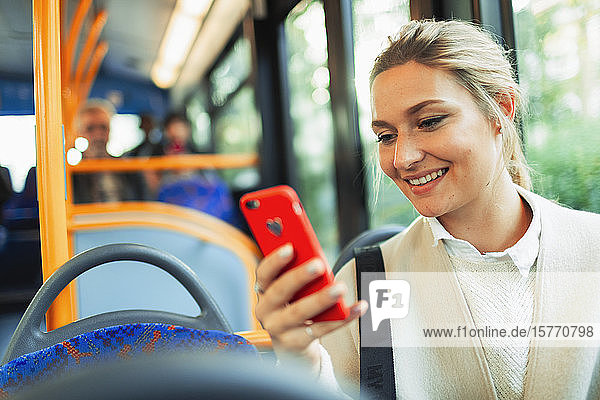 Smiling young woman using smart phone on bus