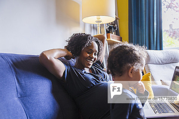 Happy pregnant mother and daughter using laptop on sofa