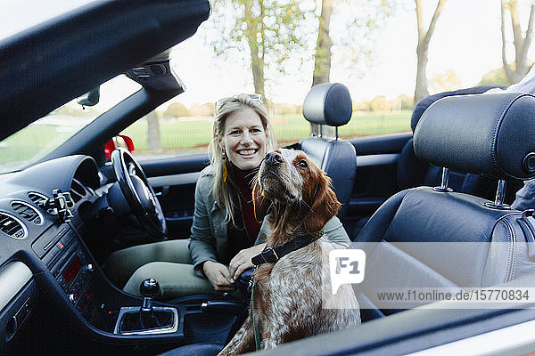 Portrait happy woman riding in convertible with dog