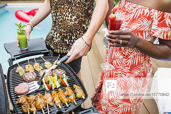 Young couple drinking cocktails and barbecuing