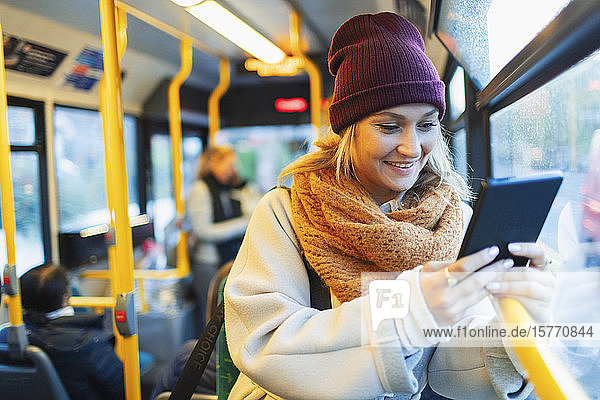 Young woman in stocking cap and scarf using digital tablet on bus