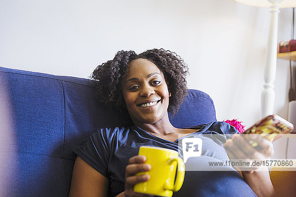 Portrait happy pregnant woman drinking tea and using smart phone