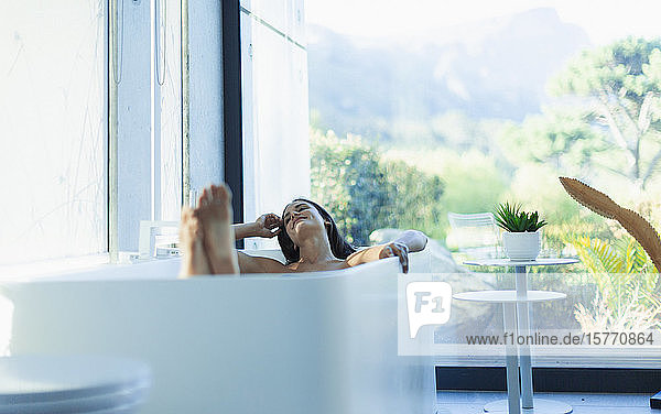 Serene woman relaxing in soaking tub in modern bathroom