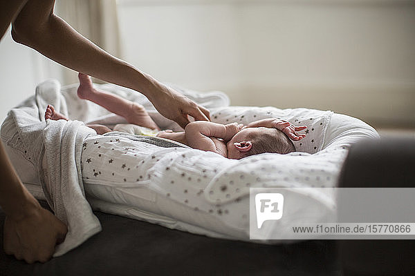 Mother reaching for newborn baby son in bassinet