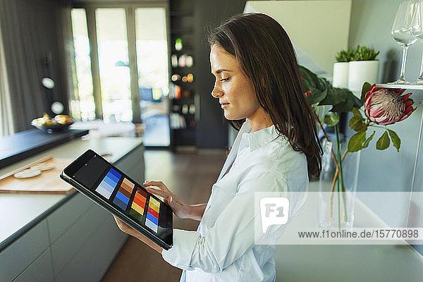 Female interior designer looking at digital color swatches on digital tablet