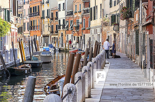 Boats moored along a tranquil canal lined with residential buildings and people talking on the walkway; Venice  Italy