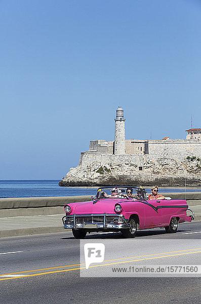 Old classic pink convertible car on the Malecon  Castillo del Morro (background); Havana  Cuba