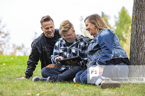 A young man with Down Syndrome learns a new program on a tablet with his father and mother while enjoying each other's company in a city park on a warm fall evening: Edmonton  Alberta  Canada